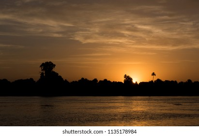 Silhouette of tropical river bank at dusk sunset with palm tree and sun in orange sky