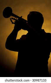 A silhouette of a trumpet being played by a trumpet player in the vertical format with copy space and a gold background.
