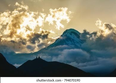 Silhouette of Tsminda Sameba or Holy Trinity Church near the Kazbegi and Gergeti village, Georgia. Kazbek mountain and cloudy sky on background.