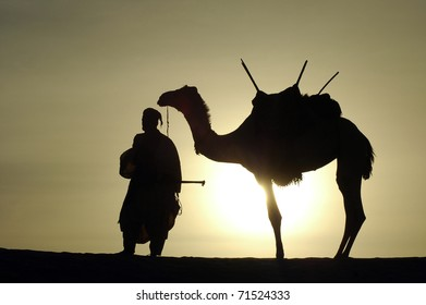 A silhouette of a Tuareg nomad standing next to his camel in the desert
