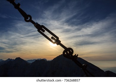 Silhouette of turnbuckle securing wires in the mountains, sunrise