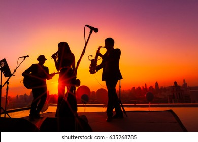 Silhouette twilight scene trio musician singing on skyscraper terrace. Trio band showing on sunset light. Background for new year party or celebration concept. Bangkok Thailand