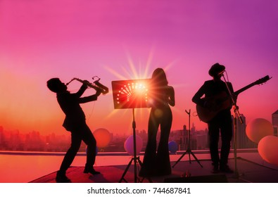 Silhouette twilight summer scene of three musician 1 woman / 2 men, Trio band showing on sunset light and sky terrace with lens flare effect, image for celebration or new year party, Bangkok Thailand