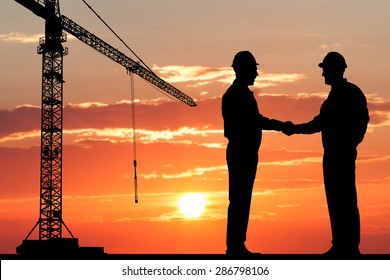 Silhouette Of Two Architect At Construction Site Shaking Hand