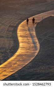 Silhouette of two bicycle riders at the Santa Monica State Beach in California.