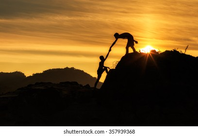 Silhouette of two boy  helping hand between climber
