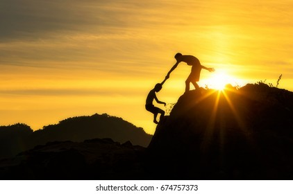 Silhouette of two boy  helping hand between climber.