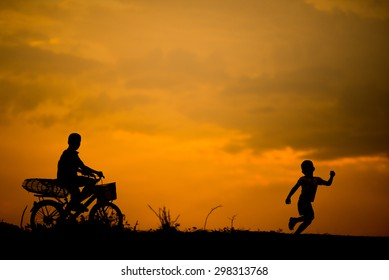 silhouette of two boys brother riding bicycle and running