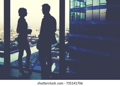 Silhouette of two business partners having conversation while standing near skyscraper window in modern interior with cityscape on background, young colleagues discuss ideas while rest after meeting