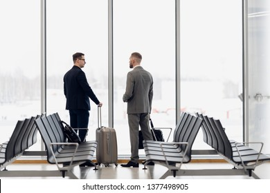 Silhouette of two businessman standing in front of a big window at airport at wating area near departure gate