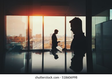 Silhouette of two businessmen working with their gadgets in office interior of skyscraper, man in front with digital tablet and man behind with phone, cityscape outside, strong reflections