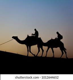 Silhouette of two camel riders near Dubai