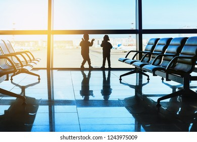 Silhouette of two children standing in the airport looking at airplanes in the window