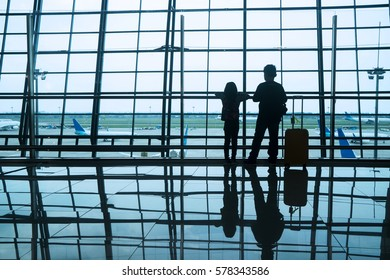 Silhouette of two children standing in the airport while looking at aircraft on the window