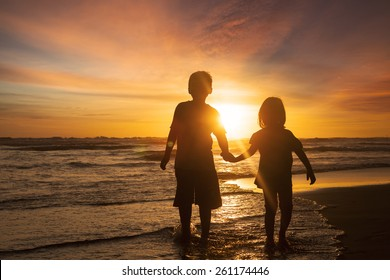 Silhouette of two children walking on the beach while holding hands with sunset background on the back