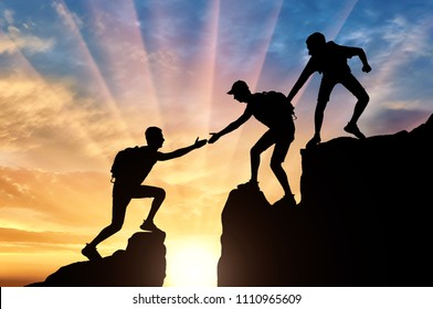 Silhouette of two climbers in the mountains help another climber to overcome the obstacle. Conceptual image of a helping hand
