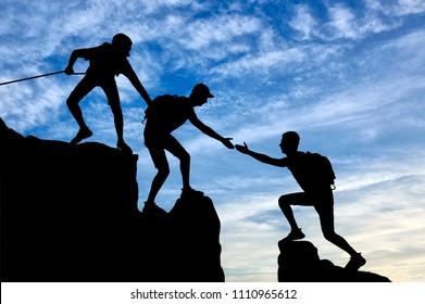 Silhouette of two climbers in the mountains help another climber. Conceptual image teamwork