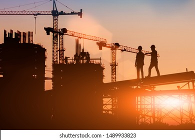 Silhouette Two engineers consult and inspect high-rise construction work over blurred industry background with Light fair.