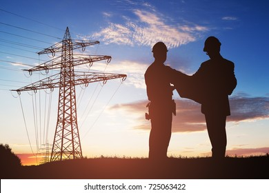 Silhouette Of Two Engineers Discussing Together With Electricity Pylon In Background