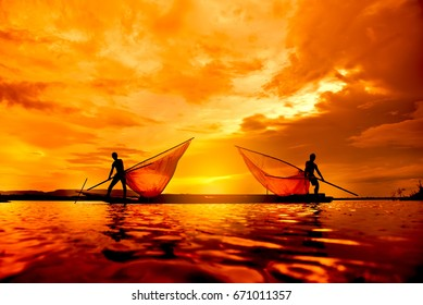 Silhouette Two fishermen with nets on a fishing boat at sunset.