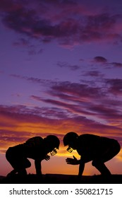 A silhouette of two football players getting ready to hit in the outdoors