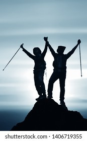 silhouette of two friends having achievement climbing up mountain to the peak together with background of sunrising