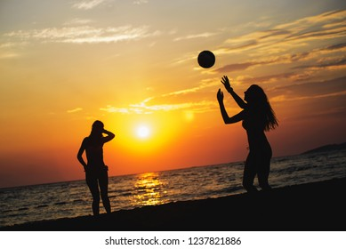 Silhouette of two friends playing beach Volleyball on the beach in sunset