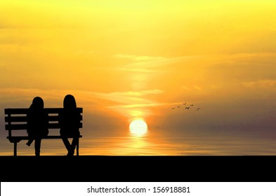 Silhouette of two friends sitting on wood bench near beach staring at flying bird
