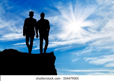 Silhouette of two gay men walking holding hands on top