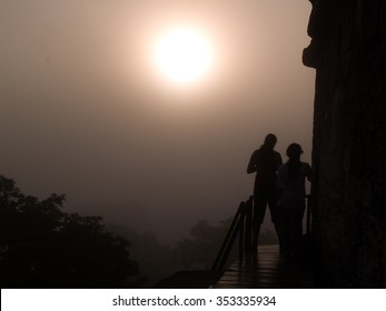Silhouette of two girls on the top of a mayan temple at sunrise in Tikal Guatemala