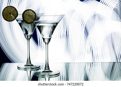 silhouette of two glasses with a cocktail and lemon in a nightclub