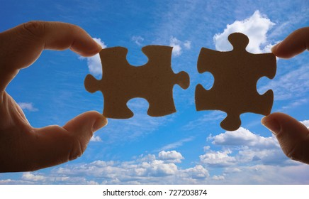 Silhouette of two hand holding couple of jigsaw puzzle piece  on blue sky with clouds background. connection idea, sign, symbol, concept