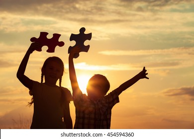 Silhouette of two happy children which playing on the field at the sunset time. They having fun on the nature. Concept of the kids are ready to go to school.