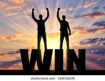 Silhouette of two happy men with raised arms standing on the word win. The concept of winning and mutual benefit of business partners
