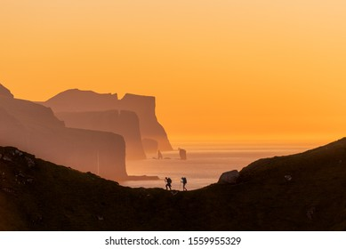 The silhouette of two hikers set against a stunning orange sunset sky overlooking The Giant And The Witch sea stacks in the background at Kalsoy, Faroe islands. Taken September 2019.