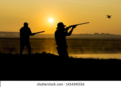 Silhouette of a two hunters against the yellow evening sky. Stands at the ready with a gun, aims at flying game.