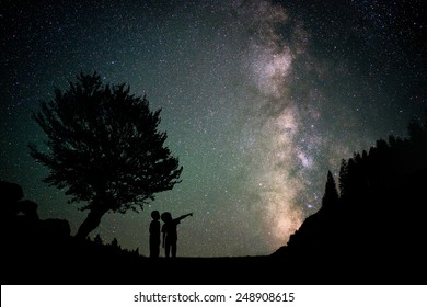 Silhouette two little boys with Milky Way and beautiful night sky full of stars in background