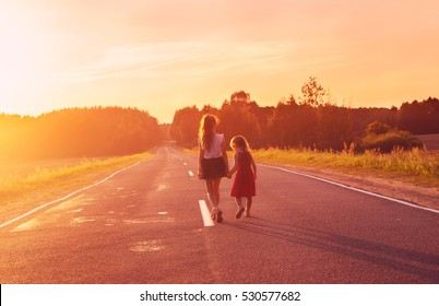 Silhouette two little girls walking on the road . Sisters enjoyed a Holiday over blurred summer nature. Concept People and nature.