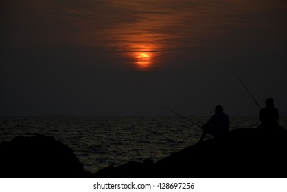 silhouette of two man fishing at sea while sunset.