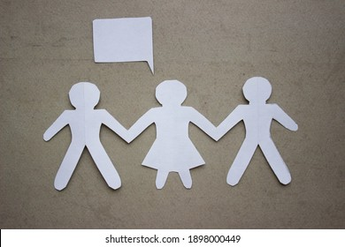 Silhouette of two man and woman between them, holding hands, cut out of white paper. With speech-bubble. In the center of the photo on a beige background.