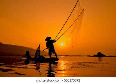 Silhouette two men fishing on a fishing boat in the Mekong River at sun rise