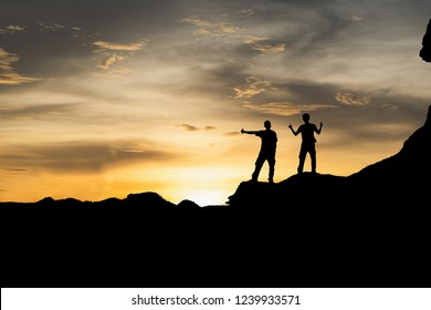 Silhouette two men standing on the mountain with a happy expression,People top on a mountain.