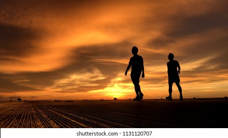 Silhouette of two men walking on platform with golden clouds during sunset background.