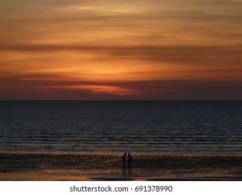 Silhouette of two people at beach at beach during sunset