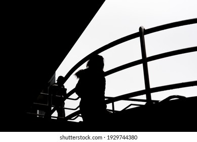 A silhouette of two people going down the stairs - Shutterstock ID 1929744380