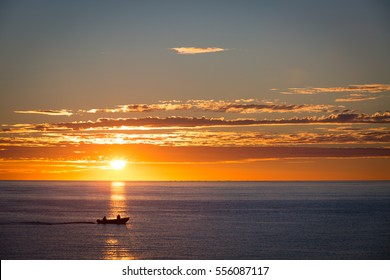 Silhouette of two people in a local small fishing boat moving with sunrise in the background on the Sea of Cortez near Los Barriles, Mexico on the Baja Peninsula.