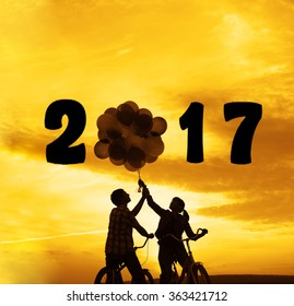 Silhouette of two people on romantic date looking each other Young couple sitting at bicycle Girl holding balloons on sunset  sky trees park background. Copy space for inscription. 2017 happy new year