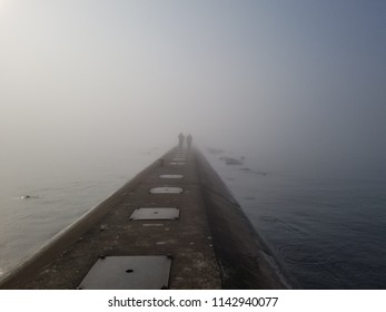 Silhouette of two people walking in the dense fog on the weathered concrete North Pier in Manitowoc, WI. Grey, quiet, secluded scene. Horizontal perspective view.