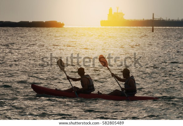 Silhouette of Two person kayaking in the sea at sunset