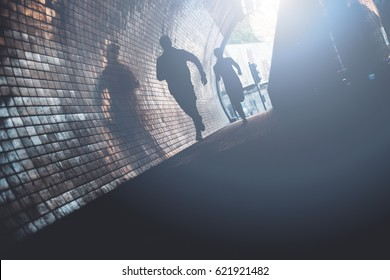 Silhouette of two running athletes inside the tunnel. Man and woman jogging in the city. Intentional extremely dark colors, little motion blur